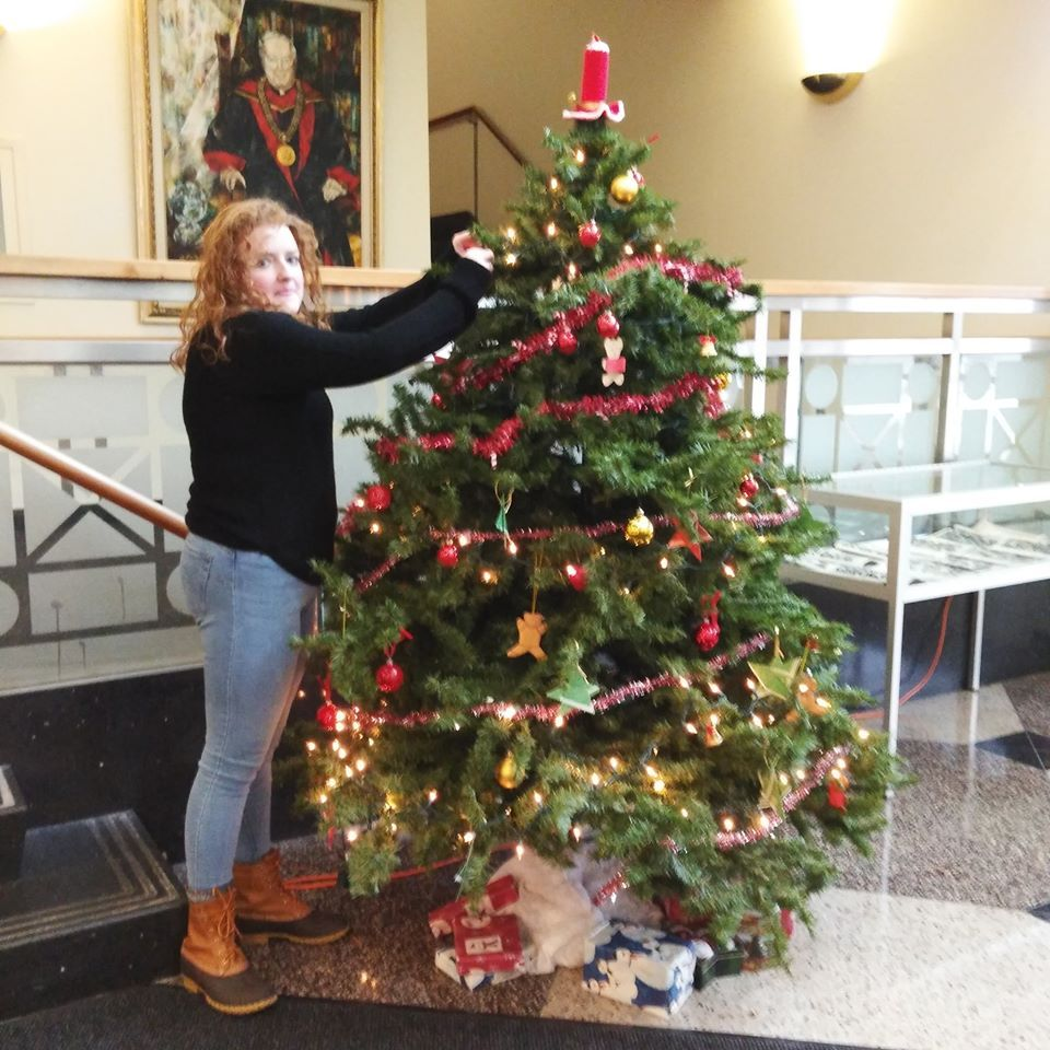 worker Molly rearranges some ornaments on the Christmas tree Looks great Very festive