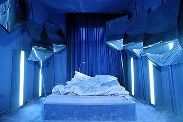 In front of an exclusively blue background mirrored sails have been set up around the bed. This room was previously called Mirrors, it was and still remains one of the earliest City Lodge favourites.  http://www.propeller-island.de/rooms_neu/room_detail/21/index.php