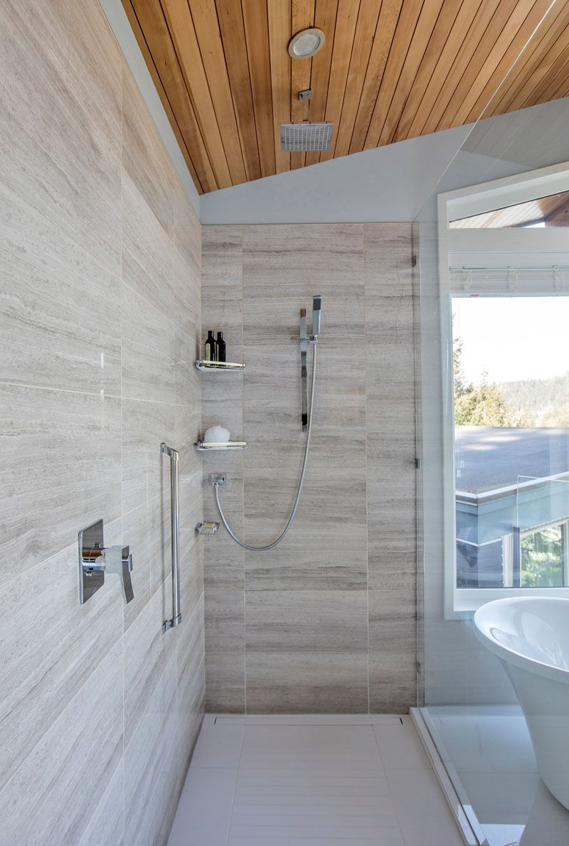 A glass shower screen separates the shower from the bath area in this modern bathroom and in the shower theres both a rain shower head and a wall mounted