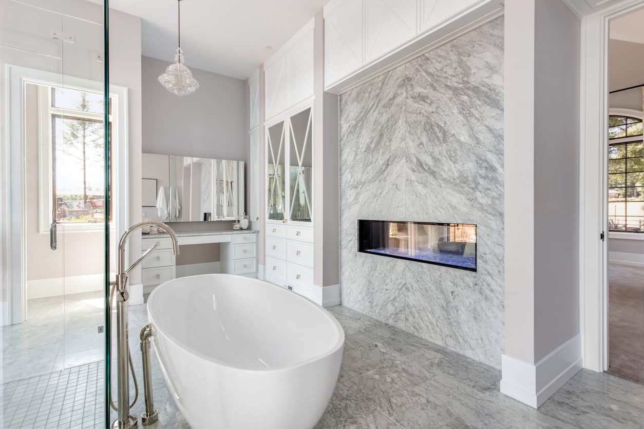 Contemporary Gray And White Master Bathroom With Floating Gas Fireplace Next To The Freestanding Tu White Master Bathroom Small Master Bathroom Bathroom Trends