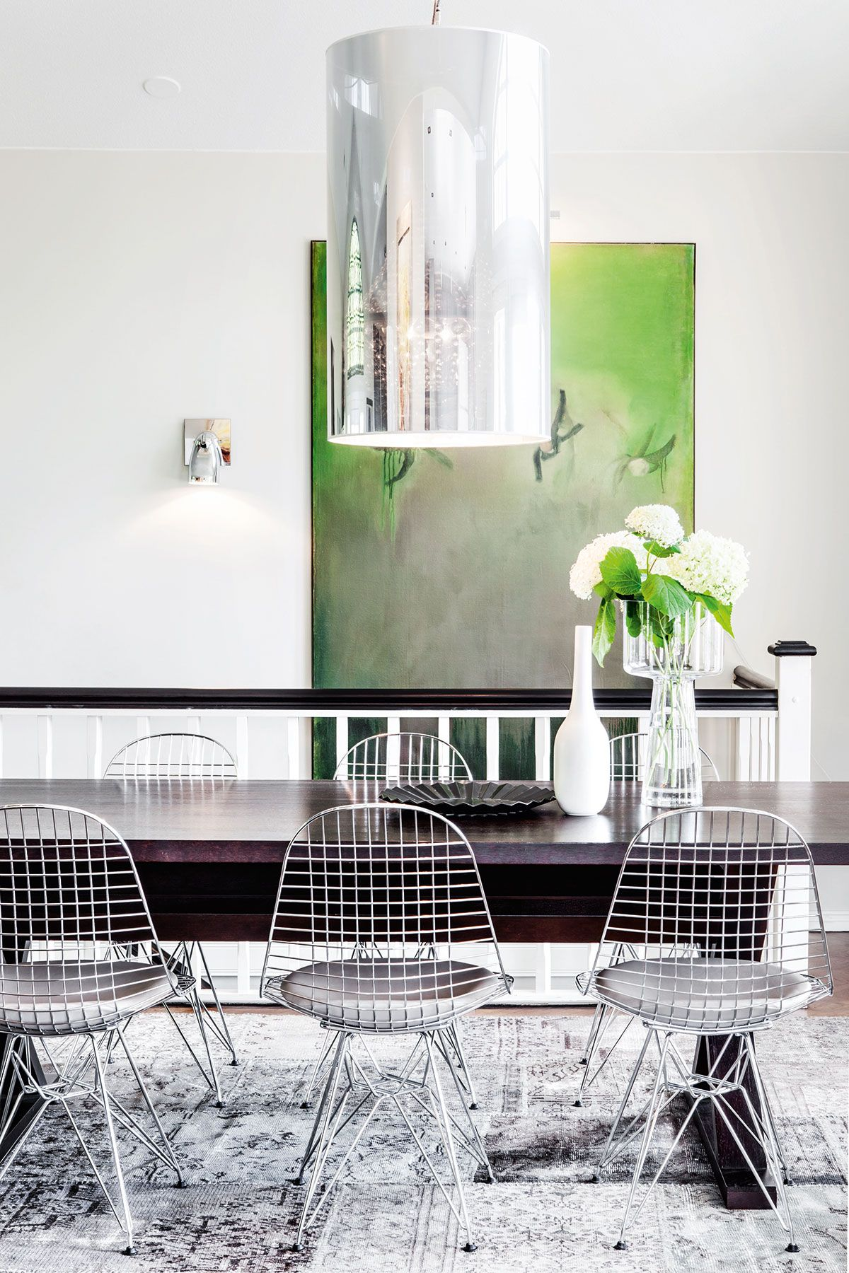 Jykevä tumma ruokapöytä on kiinnostava kontrasti Eamesin ilmavien ritilätuolien kanssa. Pöydän päällä riippuu Moooin moderni kattokruunu. Lattialla on Liffen Patchwork-matto. Taulun on tehnyt Hanne Juga.