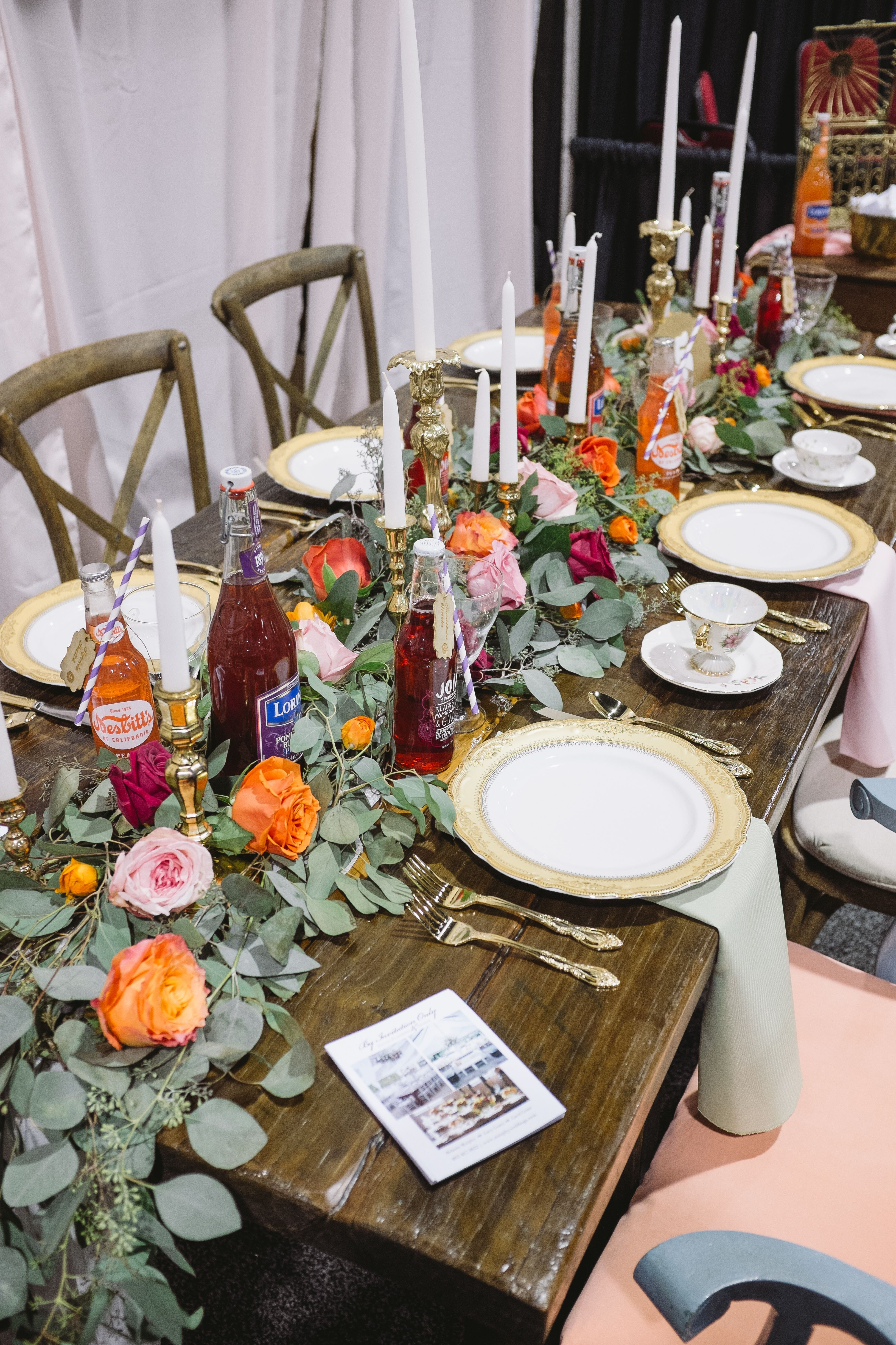 Our lovely table for the bridal show.  Eucalyptus garland with coral and pink blooms.  Vintage soda bottle seating cards