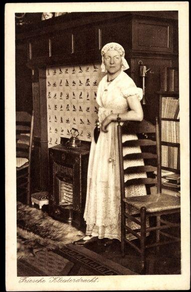 Postcard Frau in Friesischer ♥Kleidertracht, Wohnzimmer, Ofen, Teekanne