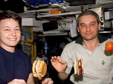 Engineering connection to digestive system. Photo shows two astronauts eating floating sandwiches and fruit aboard the International Space Station (ISS).