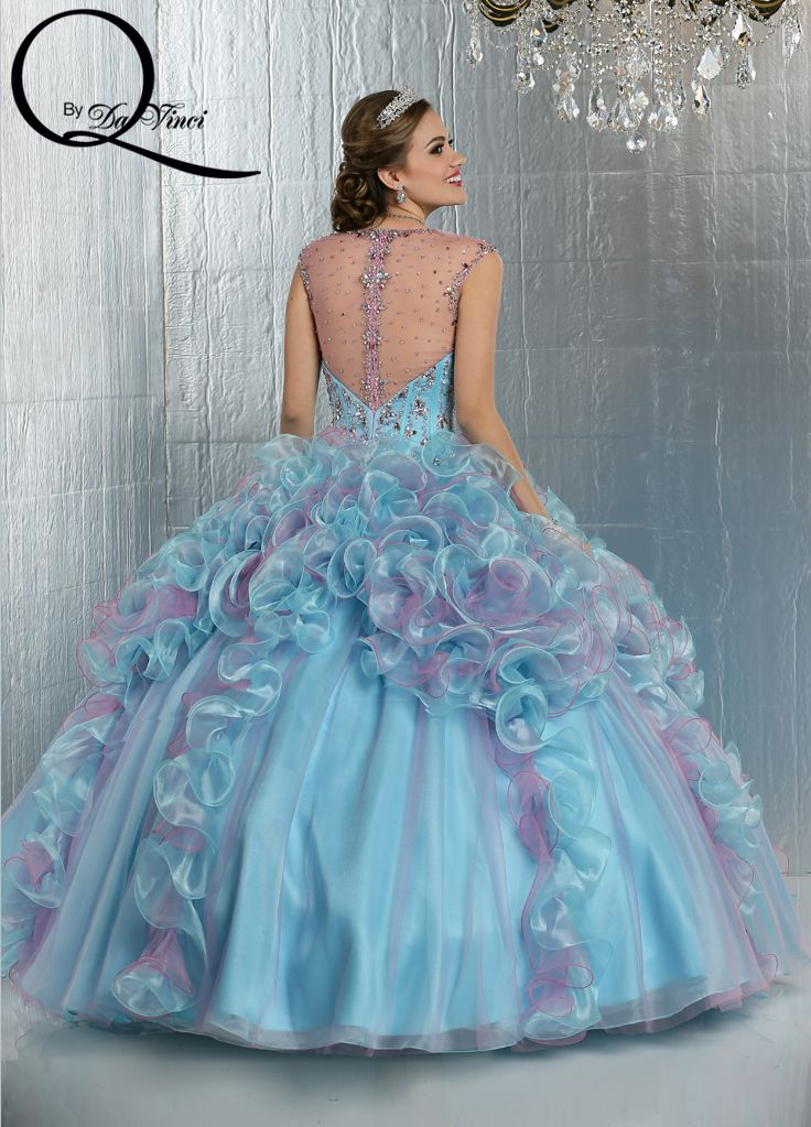 Q by DaVinci Style #: 80276 This gown features sweetheart neckline and corset style bodice accented with beading.  Beaded straps extend to a high sheer zipper back.  Ruffles of tulle and shimmer organza cover the skirt.