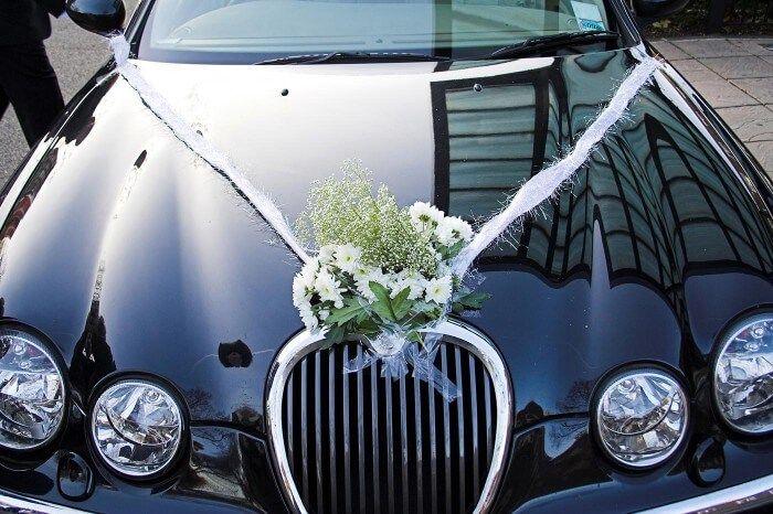Die weiße Dekoration auf dem Hochzeitauto wirkt durch die dunkle Farbe des Autos besonders elegant... #Autoschmuck # Blumen