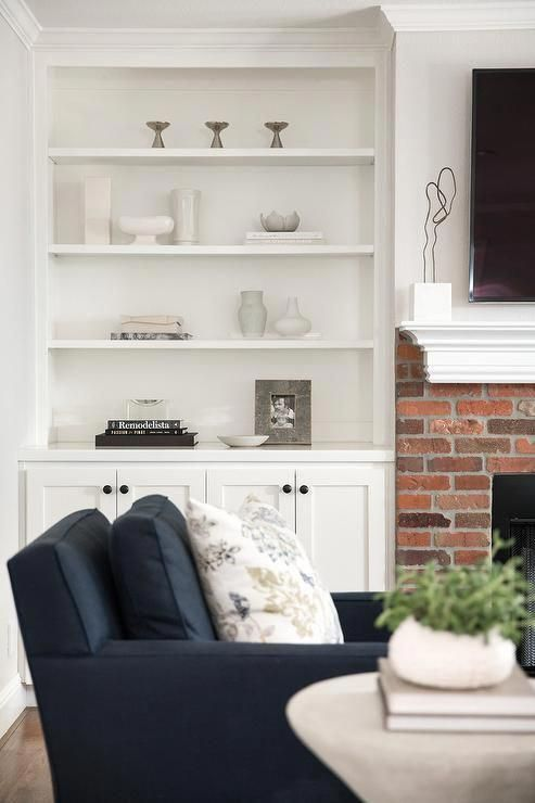 Exquisite traditional living room boasts a red brick fireplace finished with a white mantel located under a wall mount flat panel television. #tvwallmountbrick #whitebrickfireplace