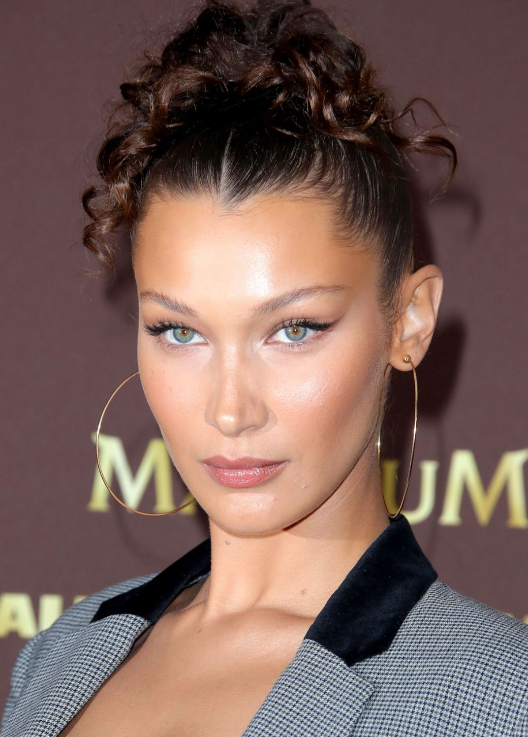 Bella Hadid glowy summer makeup look with gold earrings