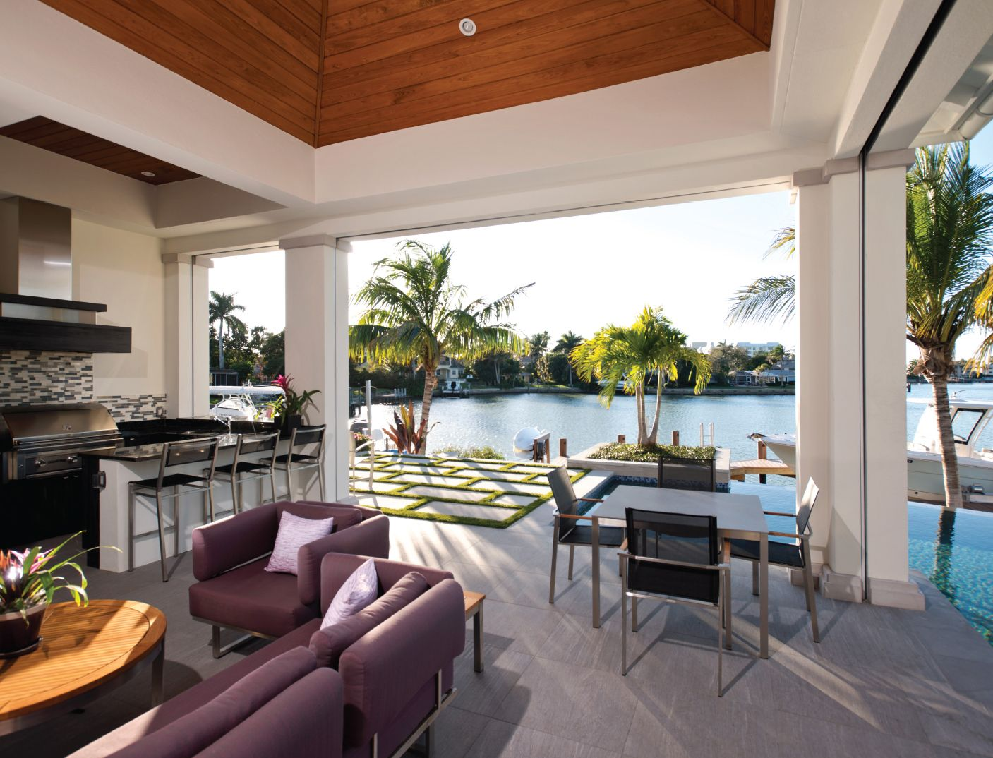 The Home S Exterior Living Space Overlooking The Water Features An Outdoor Kitchen Dining And Living Area Infinity Edge Pool A Home New Homes Living Spaces