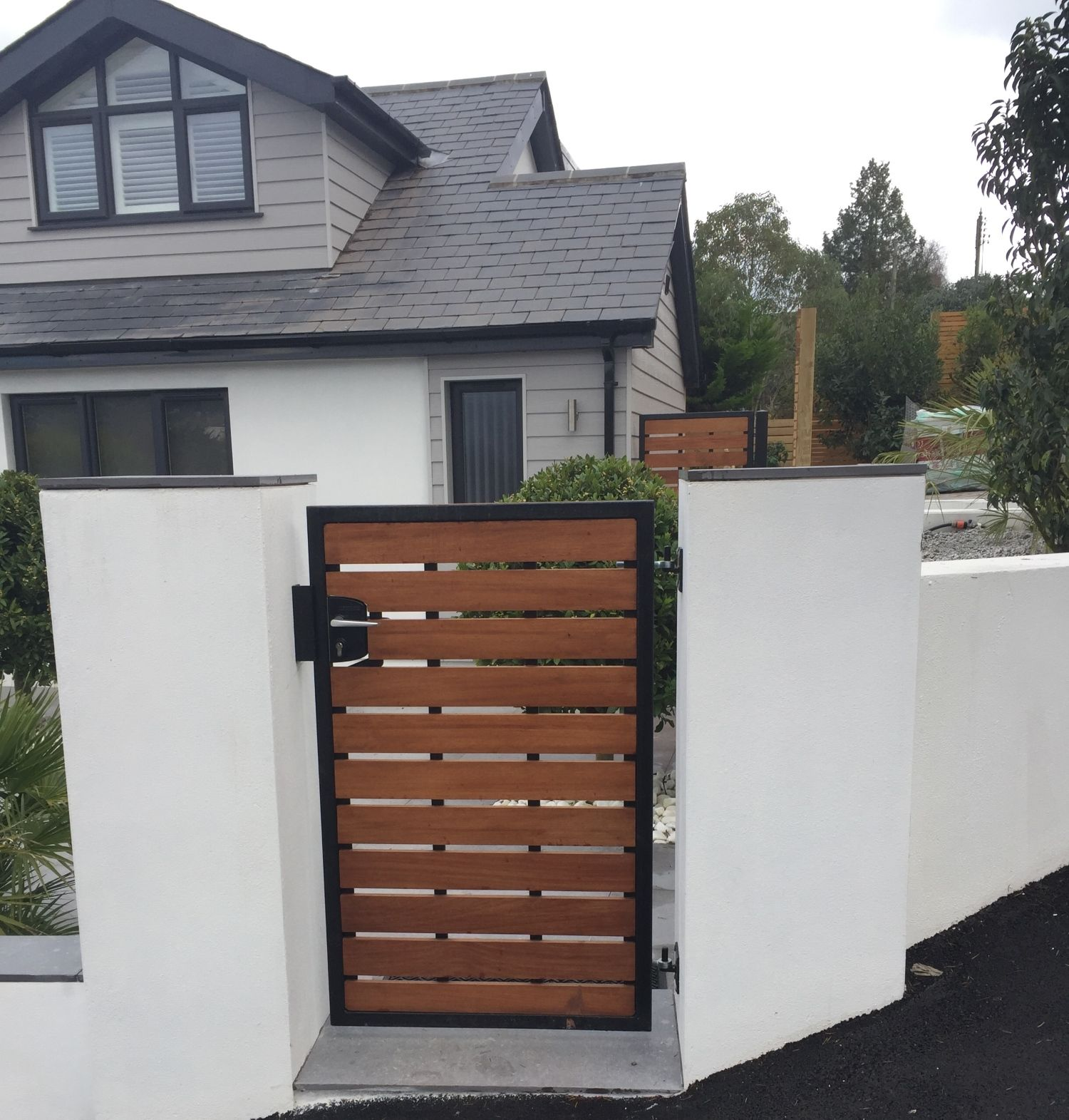 Modern garden/ side gate - the Kingston. Deep metal framed with iroko (hardwood) cladding. Fitted key lock and handle for added security. Made to any width or height in the UK. See our website for more details.