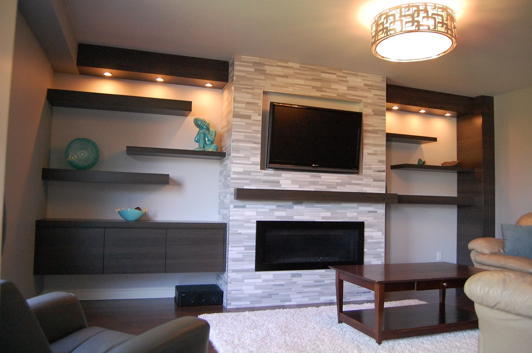 a clean contemporary living room featuring a wall mounted gas burning fireplace accented with floor to ceiling 12 x 24 large block porcelain tile