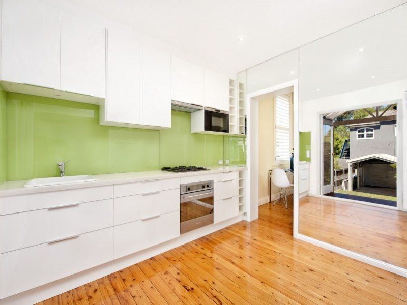 white kitchen and timber floors with a nice apple green glass