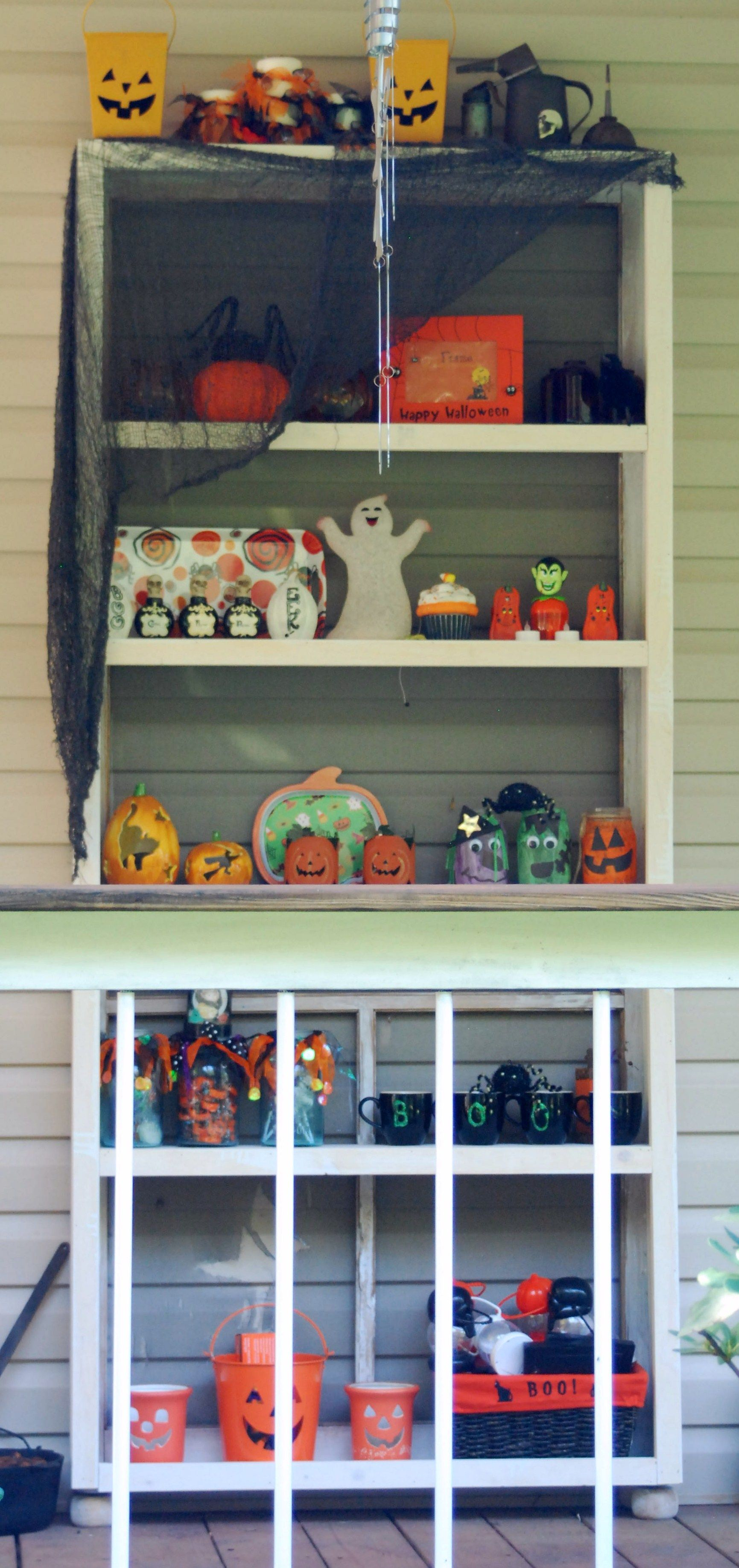 Old screen door made into shelf to display decorations on porch.
