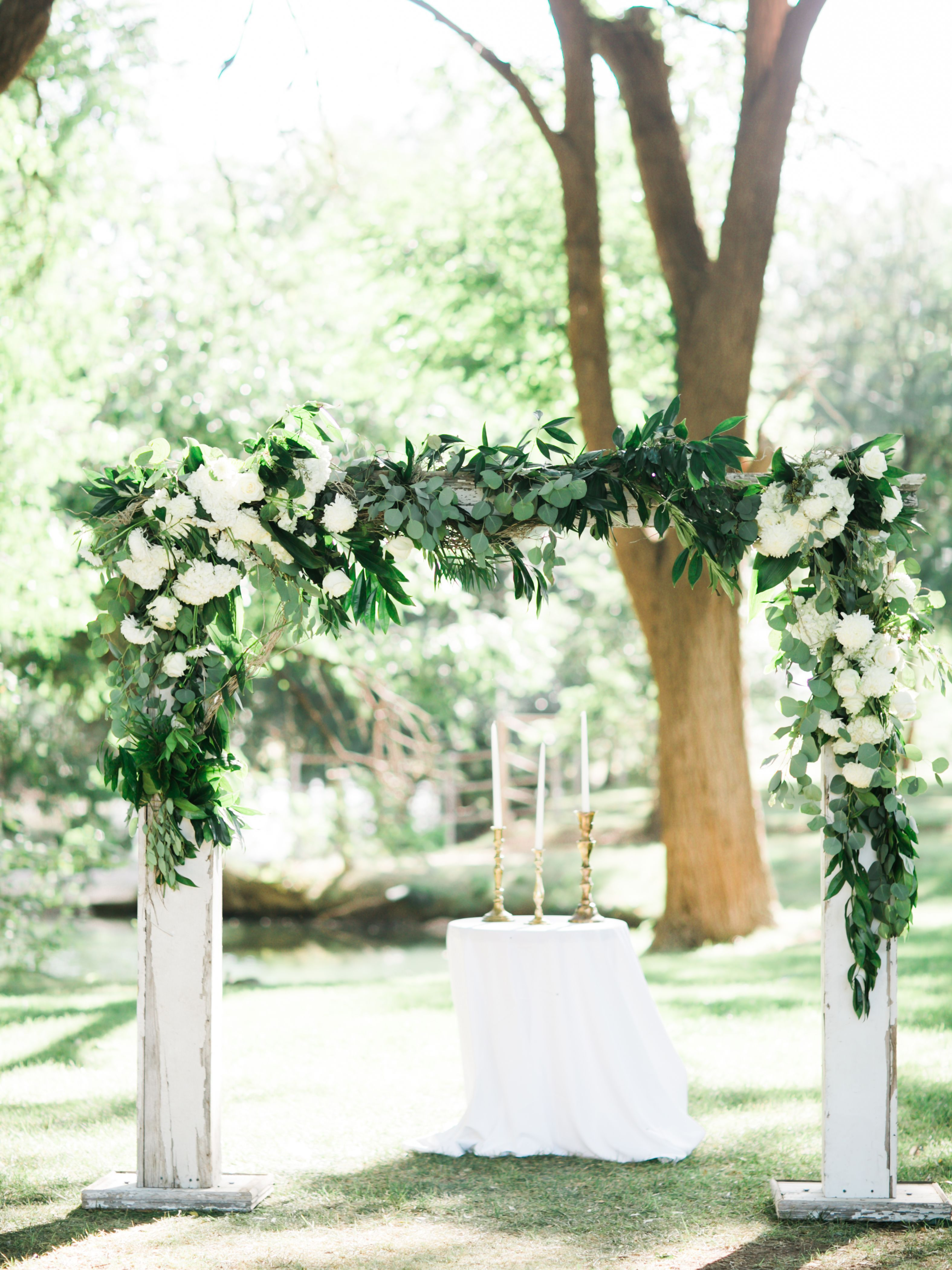 White Wood Ceremony Arch With Green Garland Green Garlands Wedding White Wedding Arch Wedding Arch Flowers