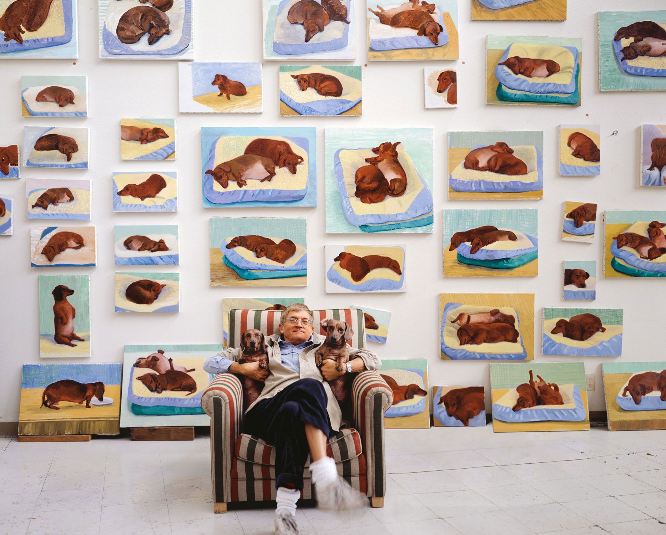 Hockney with his two dachshunds, surrounded by canvases of his two dogs.