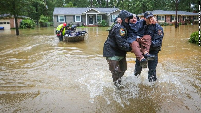 Police Officers Carry A Woman To Dry Land After She Was Rescued