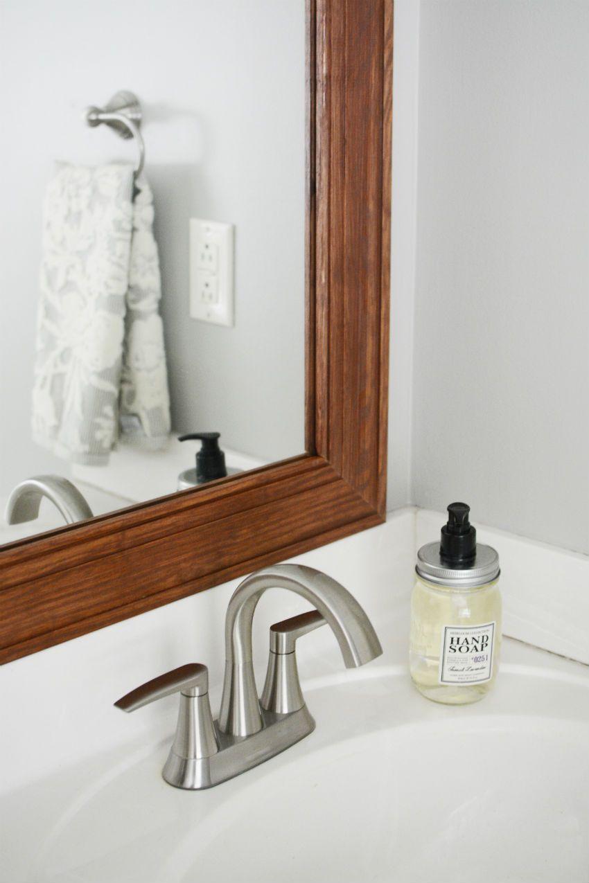 Modern farmhouse bathroom touches. Wood framed mirror, sleek faucets ...