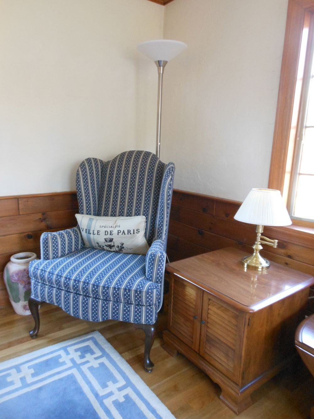 Timeless furnishings from our sudbury sale including a blue queen anne style wing back chair and a small cabinet or end table with louver doors
