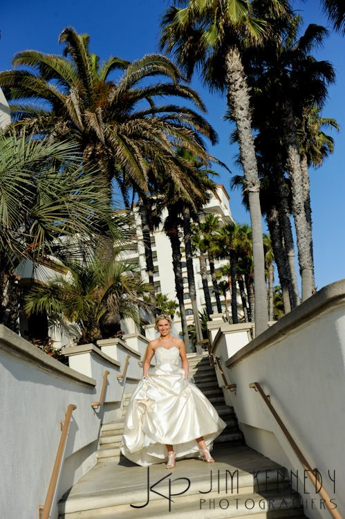 Bride on staircase outside the Waterfront Beach Resort Hilton in Huntington Beach | Jim Kennedy Photographers