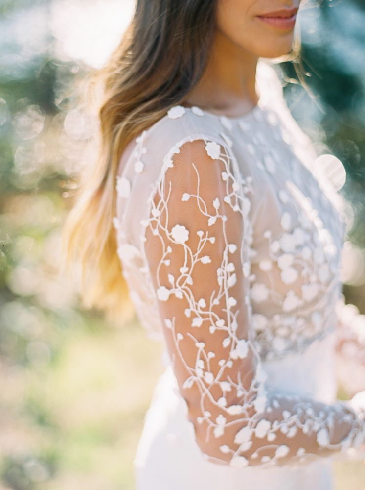 The beautiful lace pattern is a standout on the sheer sleeves of this wedding dress!