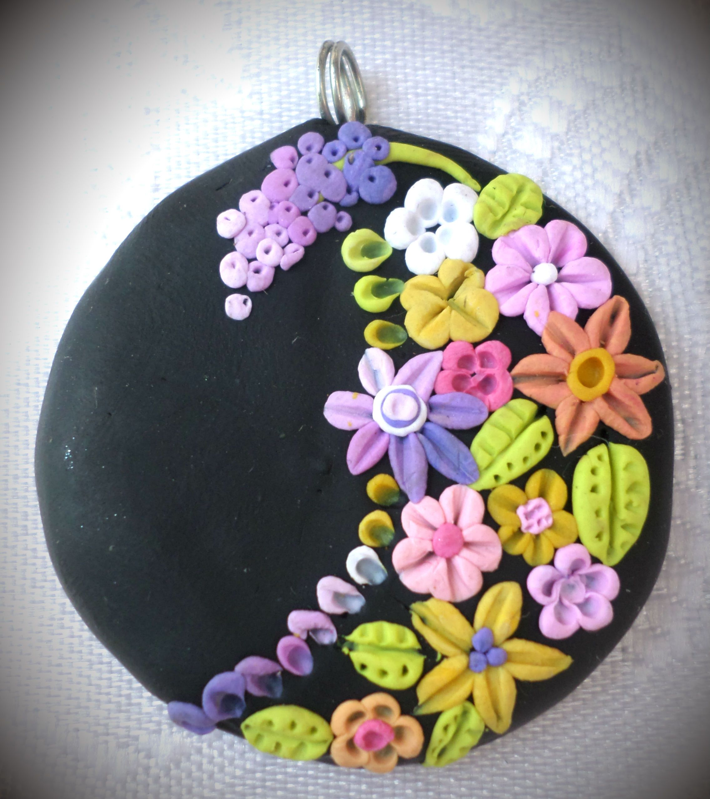 Polymer clay pendant, handmade with applique technique, one of a kind. Black, with multicolored flowers, leaves, and buds. By Lis Shteindel