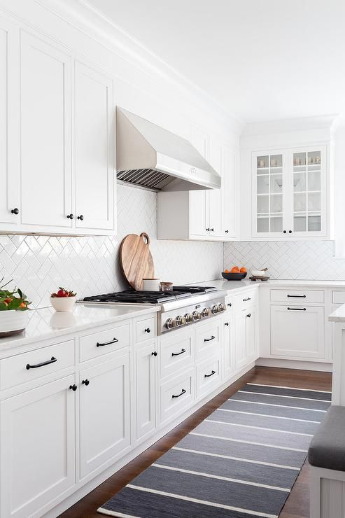 A gray ombre runner sits in front of white shaker cabinets ...