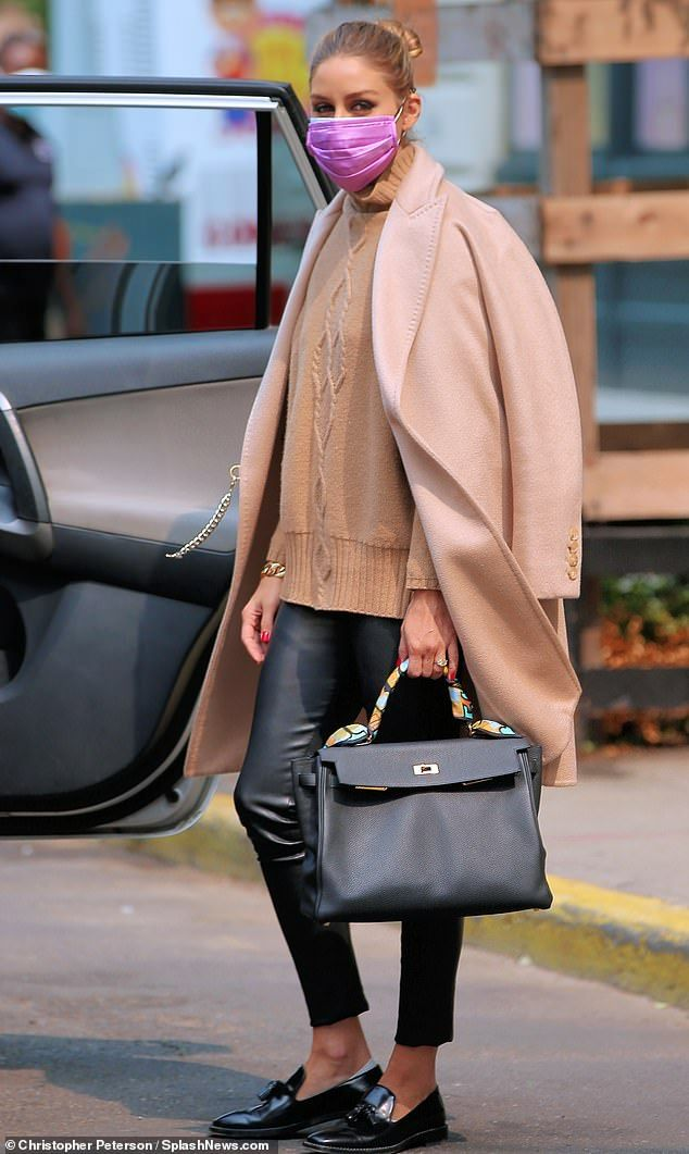Olivia Palermo looks chic in a camel coat and leat