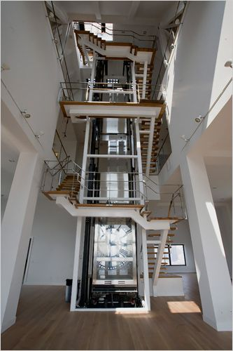 A Glass Walled Elevator And A Three Story Floating Staircase At The Center  Of