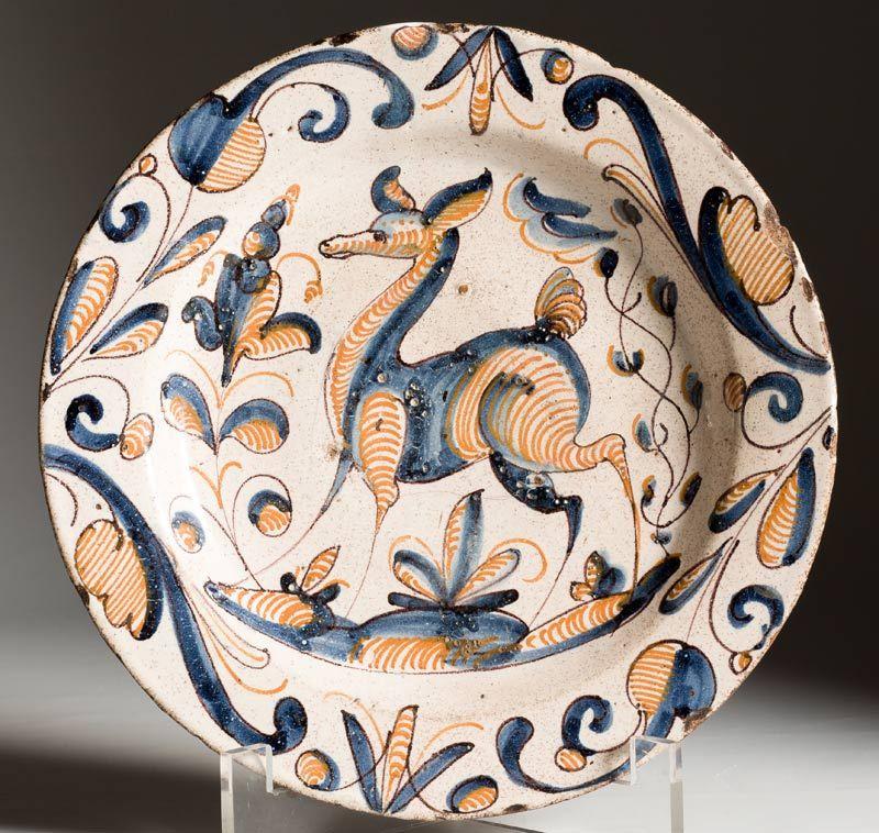 Talavera, Mediados del S. XVII. Plato en cerámica de la serie tricolor, con decoración en rayado naranja con una gacela en el asiento, rodeado por hojas. Diámetro: 34 cms.