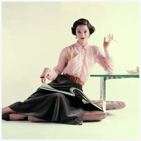 Model wearing a sheer pink shirtwaist blouse and a bell-shaped skirt by Nelly de Grab and a gilded-cage and rose quartz ring and earrings by Ballet Jewels Photo Richard Rutledge 1952