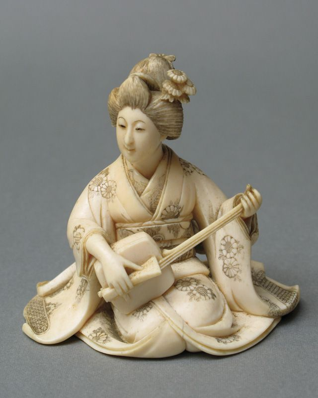 JAPANESE CARVED IVORY FIGURE, of a seated woman in traditional kimono with etched decoration, playing a stringed musical instrument. Signed underfoot. Taisho Period (after 1912). Height 3.25 inches