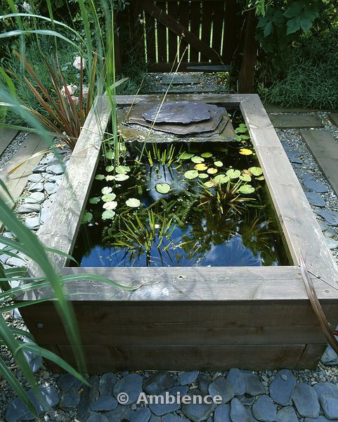 raised wooden pond with waterlilies and slate water