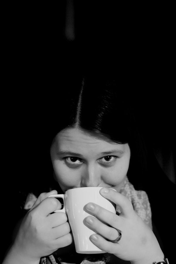 Black and White photo of a woman drinking coffee.