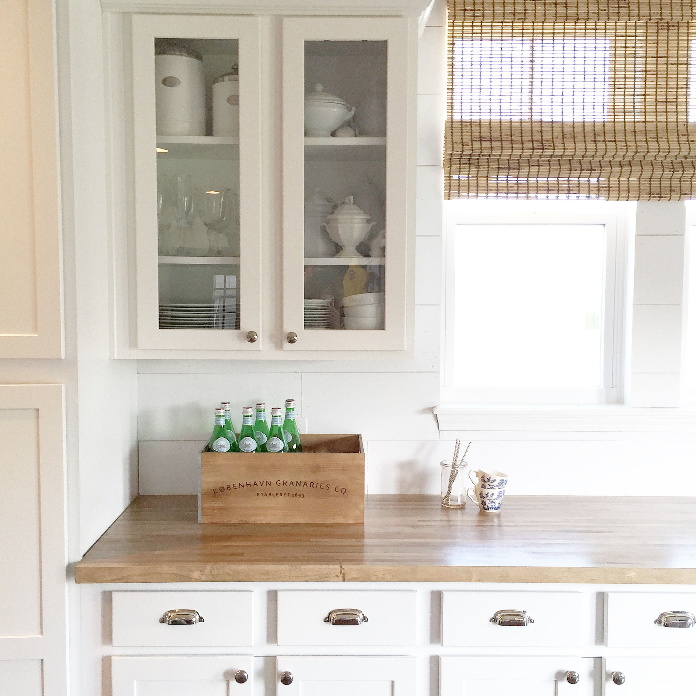 White kitchen with butcher block countertops and polishes nickel bin ...