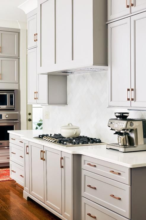A gray wood paneled kitchen vent hood stands over a white
