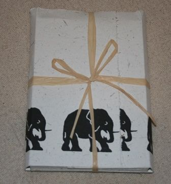 African Elephant paper dung Stationery Set. This unique gift is made from elephant dung and recycled paper, the paper is acid-free and each set is A5 size and comes with 20 sheets of handmade elephant dung paper and 10 envelopes, all decorated with a charming border of elephants.  This product is part of our Fair Trade Product List. On Sale £7.00