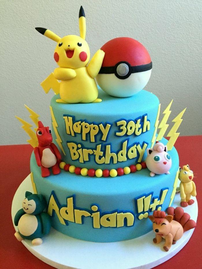 Eine Blaue Zweistöckige Pokemon Torte Ein Gelbes Pikachu Mit Roten Backen,  Ein Roter Pokeball,