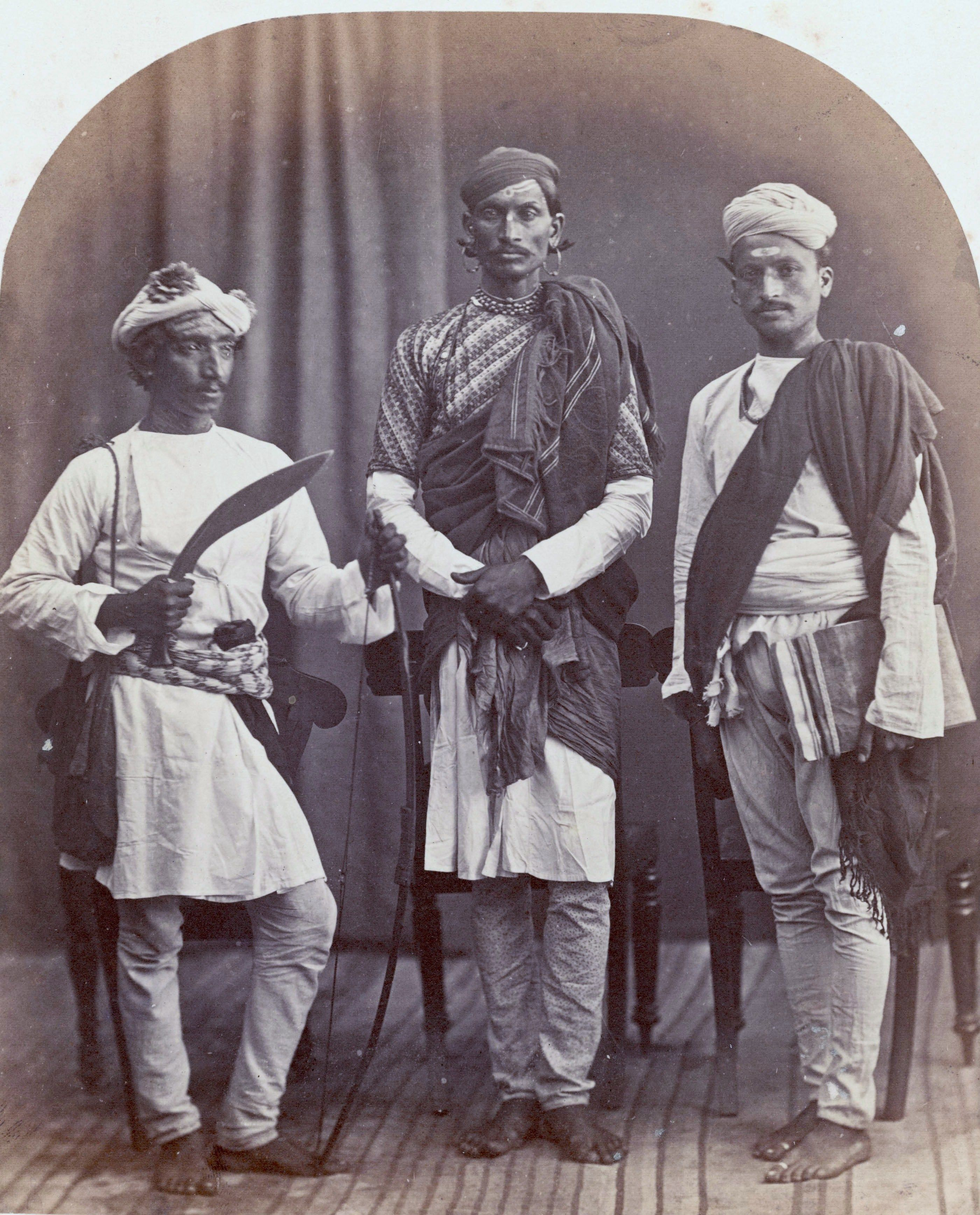 From left to right a gurkha holding a kukri a brahmin and a sood