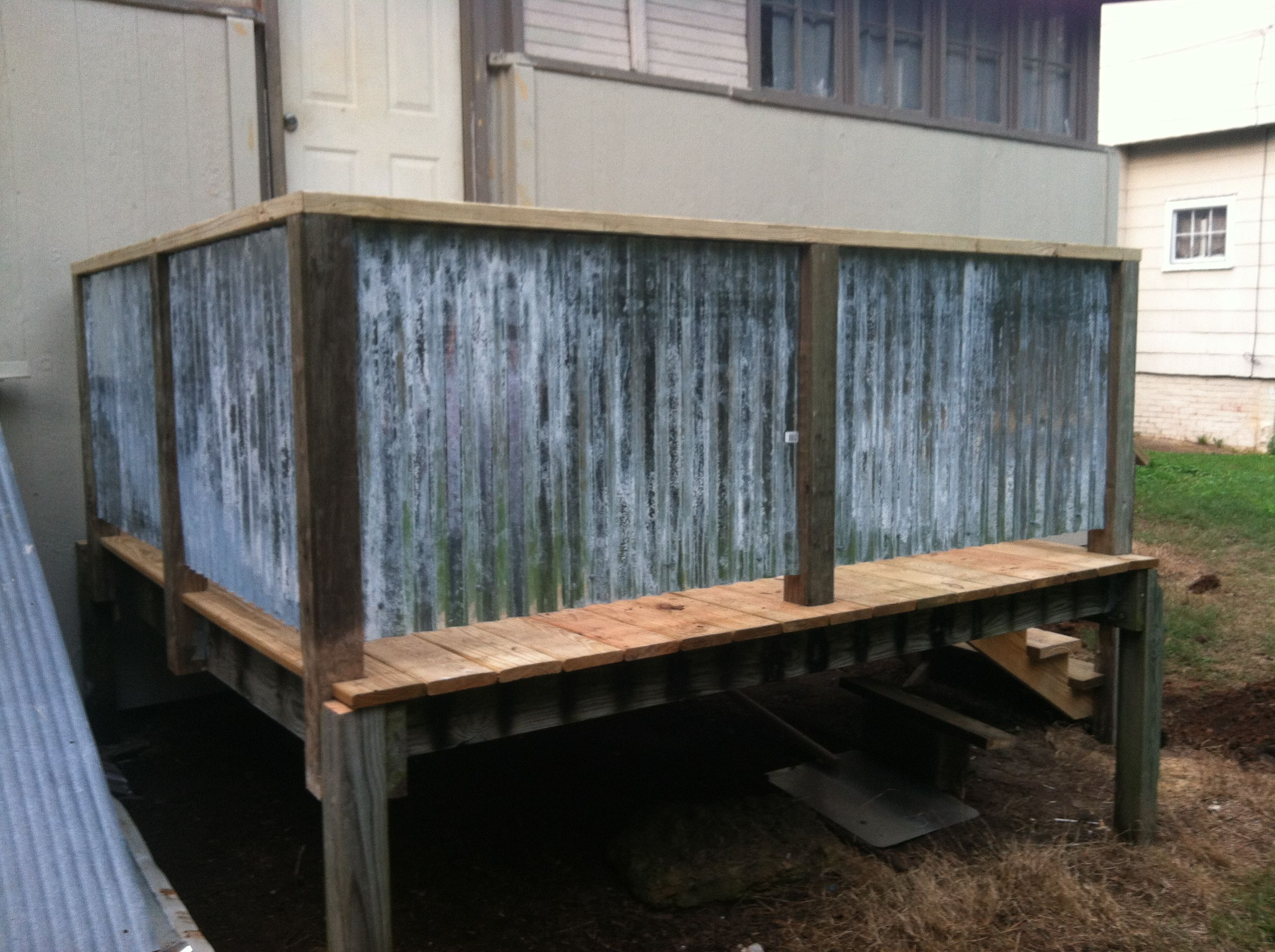 Deck with corrugated metal for railing