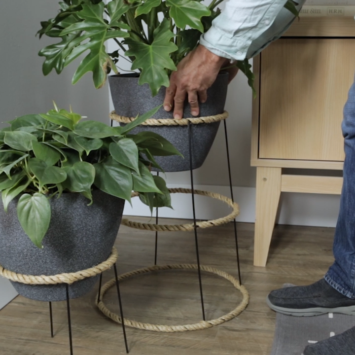 Elevated plant stands don't need to be expensive. Take a day for a DIY project to make a plant stand with an upside-down tomato cage. Dress up the metal cage with tightly-wrapped rope for added color and texture. Finish the look with a fun pot and colorful plants. #plantstand #tomatocagecraft #indoorplantstand #diy #bhg