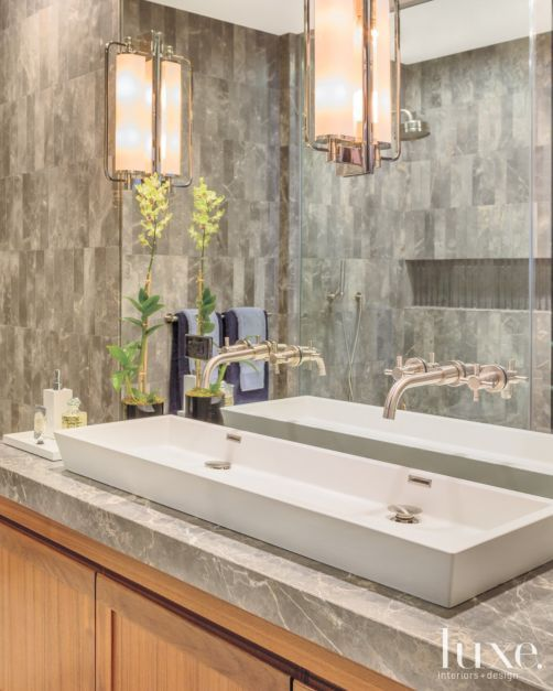 In the master bath, the Wetstyle sink is from Davis & Warshow, as are the Horus faucets. The Tall Keeley pivoting sconces are from Circa Lighting.