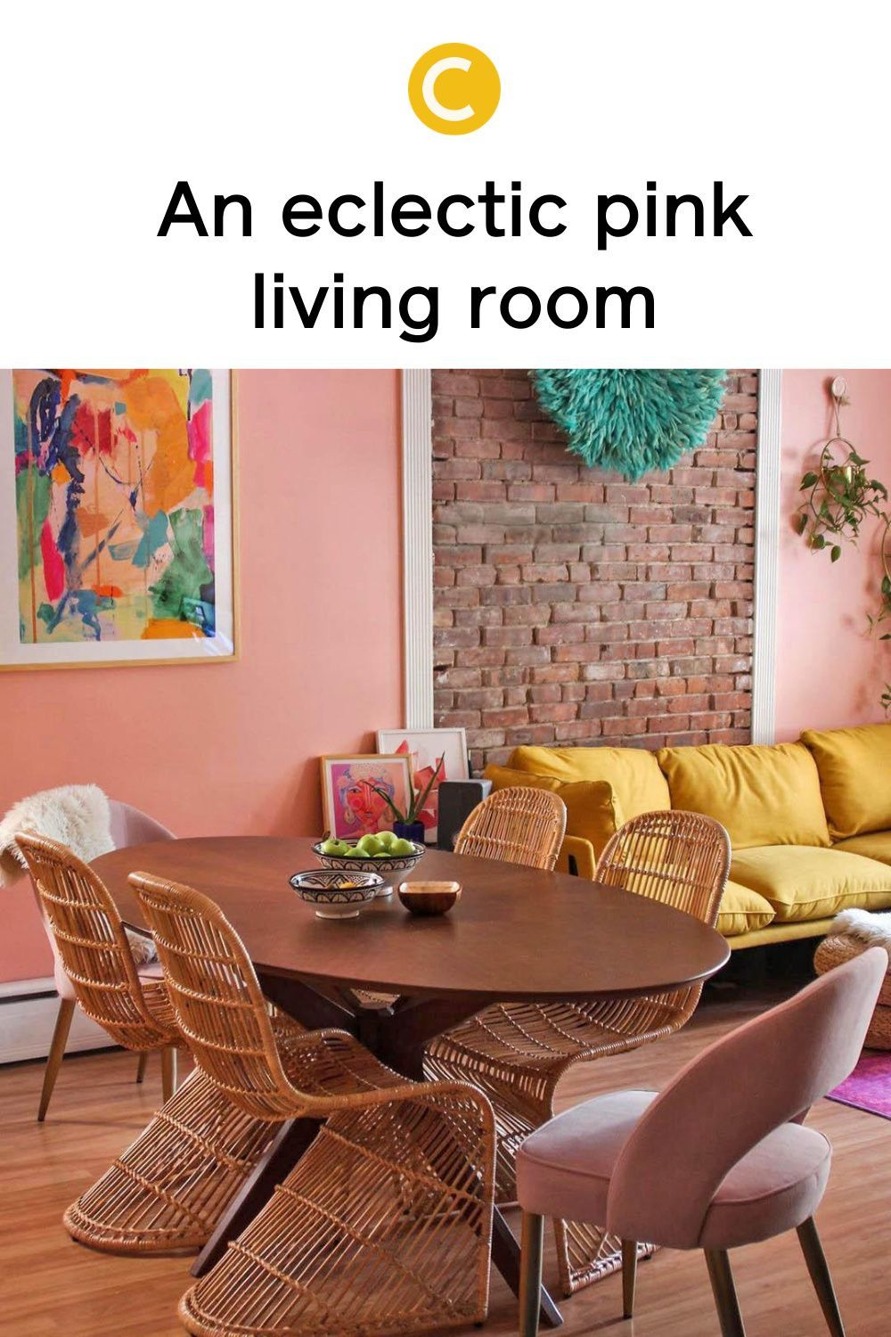 Multiple pink paints, a bright yellow couch, and other vibrant decor elements make this eclectic boho living room a space bursting with color. Get inspired to try this color palette now on our blog. #livingroomdecor #eclecticdecor #bohodecor