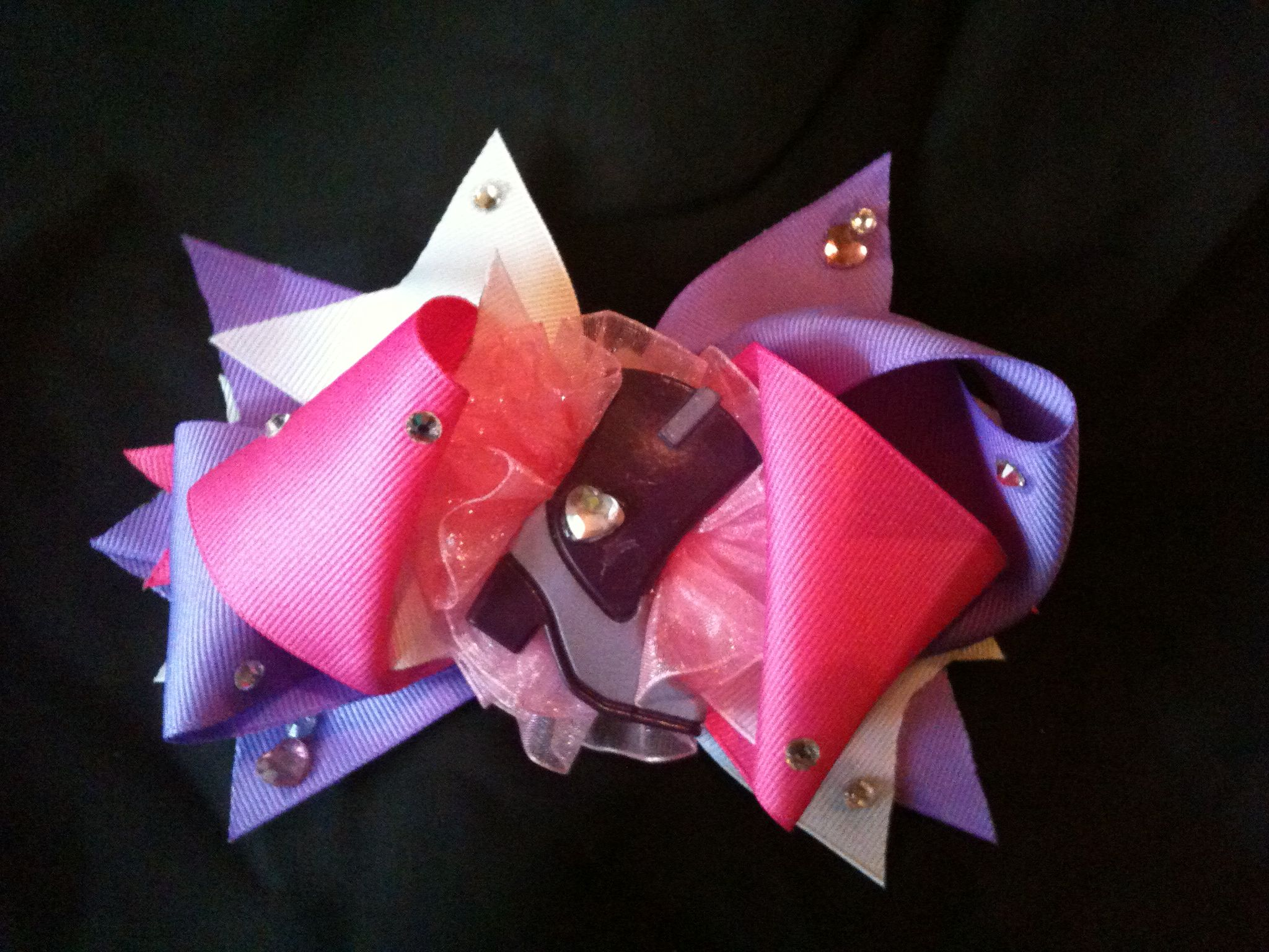 Pink,purple, and white rodeo bow with bling and boot center