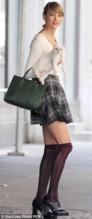 What's new pussycat: Swift looked sophisticated in a long sleeved white top and checked mini skirt teamed with maroon stockings