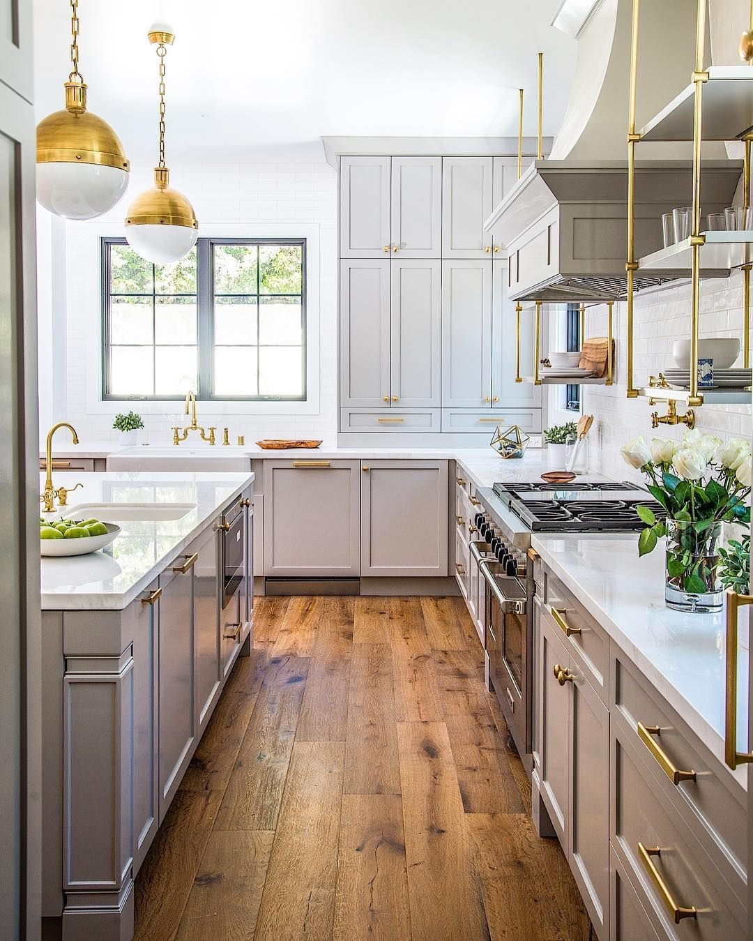 Plank hardwood floors and bronze fixtures give this kitchen great ...