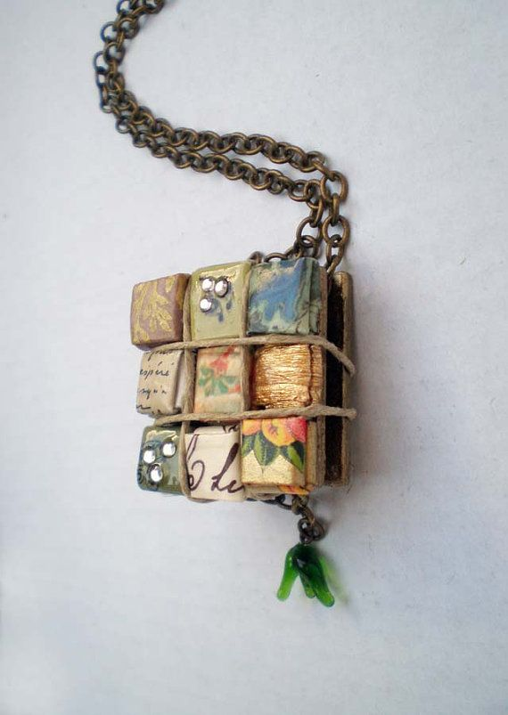 Colorful, decorative papers from around the world give this unique paper necklace global appeal.    Beautiful papers from places like Italy, India, and Japan are folded into tiny squares and nestled on golden patina wood to create a kaleidoscope of color. Rhinestone squares are designed and crafted from recycled paper by Coco Delay.    A glass vintage charm dangles gently at the bottom. Pendant hangs from 18 adjustable antique bronze chain (nickel and lead-free). Light yet sturdy. Water…