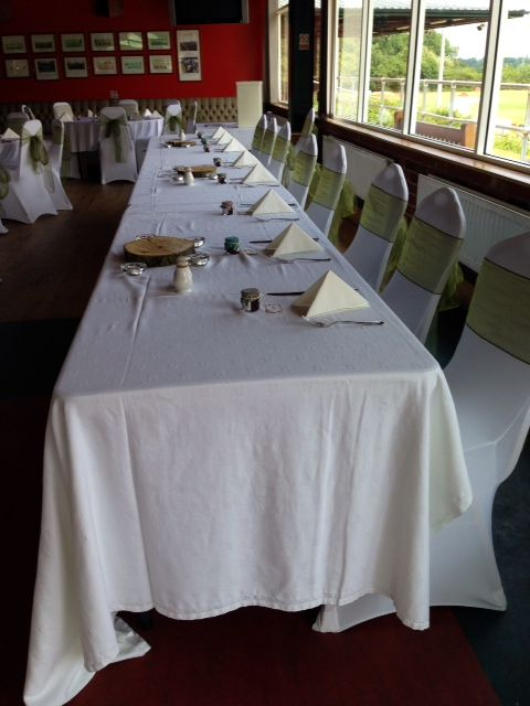 White chair covers, sage green sashes