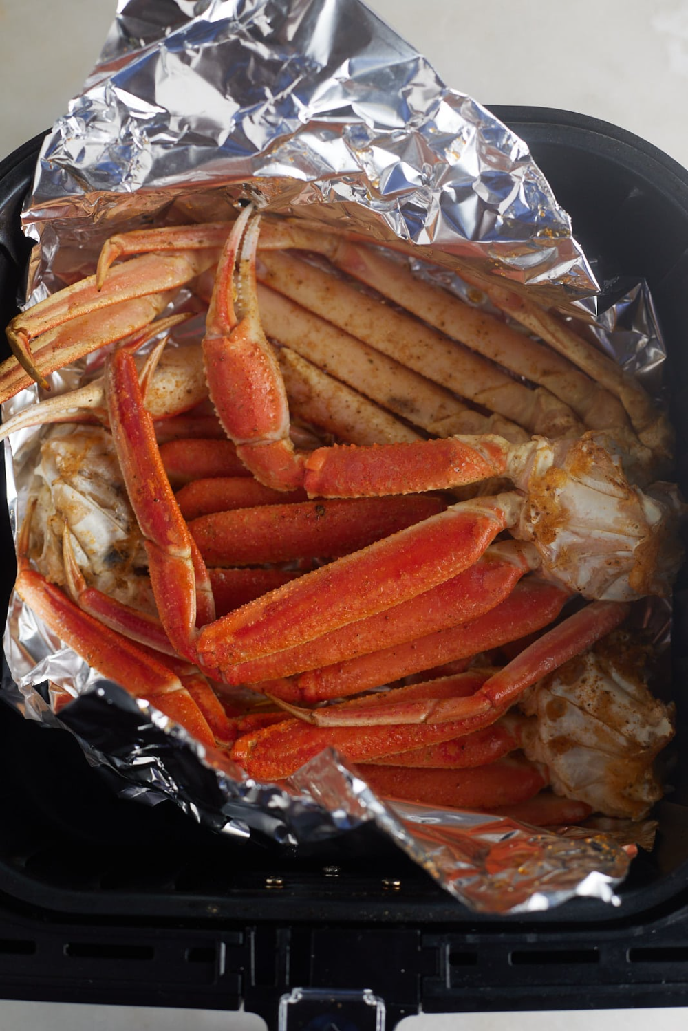 The Cooked Crab Legs On Foil In The Air Fryer Basket Air Fryer Dinner Recipes King Crab Legs Recipe Air Fryer Recipes Easy