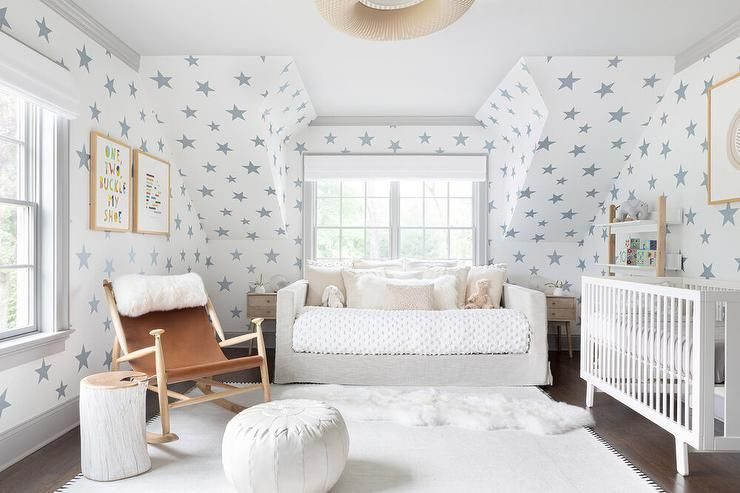 Sweet gender neutral nursery features a gray linen daybed placed beneath a windo...