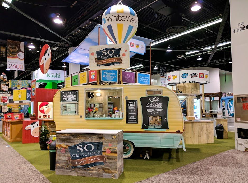 The WhiteWave Foods exhibit at the Natural Products Expo West show 2017 was designed to mimic a food festival. String lights, food trucks, bright graphics and various walk-up kiosks were made to look whimsical and fun while maximizing sampling space and branding.